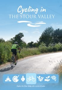 Photograph of a man cycling up a shallo winclude in a sunny landscape