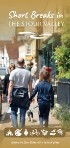 Photograph of a father and son walking along a village street on a sunny day