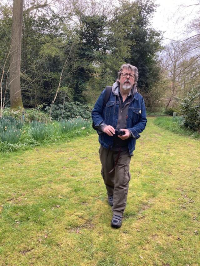 Geoff Nicholson walking in a garden
